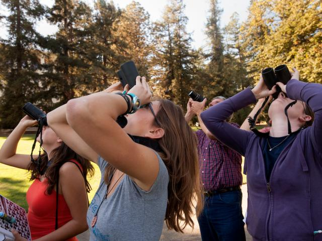 Students birdwatching with binoculars in the Arboretum